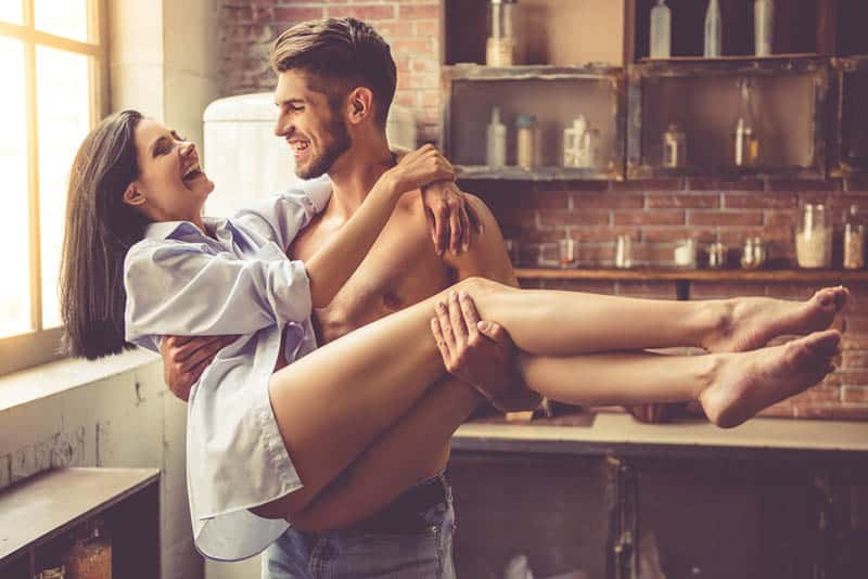 man holding smiling woman in arms at home