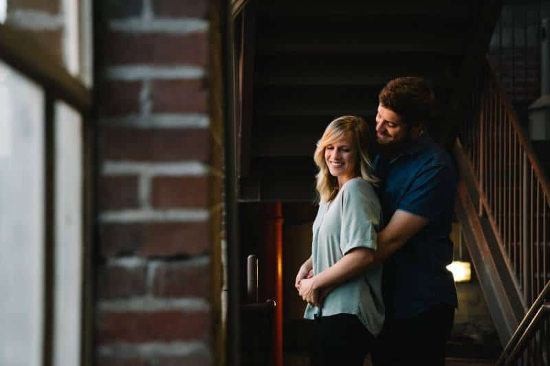 man hugging woman from behind at home