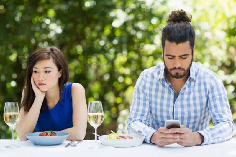 man ignoring his girlfriend and using phone