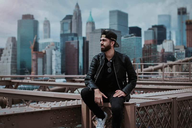 man in black leather jacket standing on top of bridge with city buildings behind him