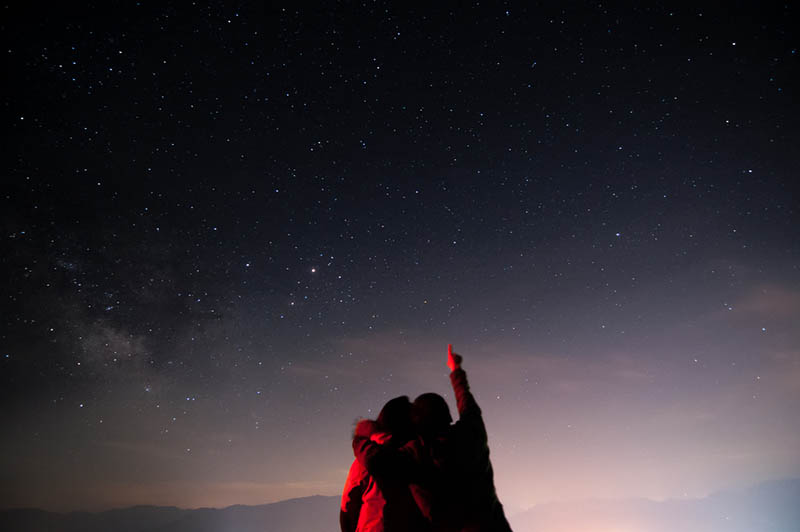 man pointing on stars while hugging a woman