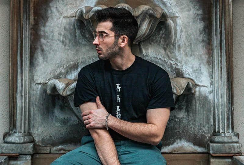 man wearing black tshirt and eyeglasses looking away