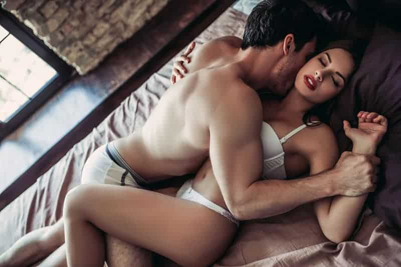 passionate couple kissing on the bed
