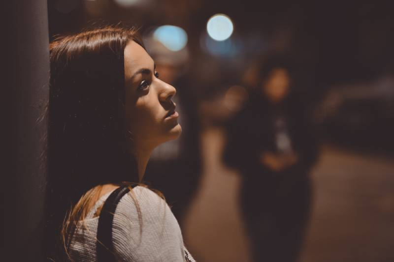 portrait of thoughtful women leaning against street