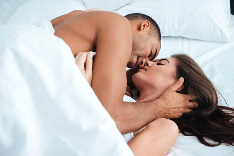 romantic couple lying on bed under blanket