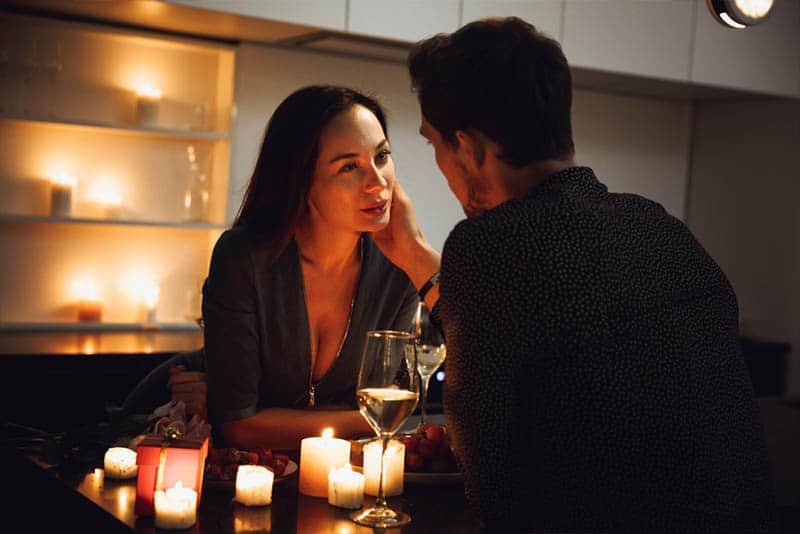 romantic couple sitting on table with candles