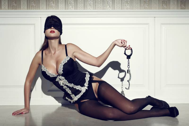 sexy woman with covered eyes holding handcuffs