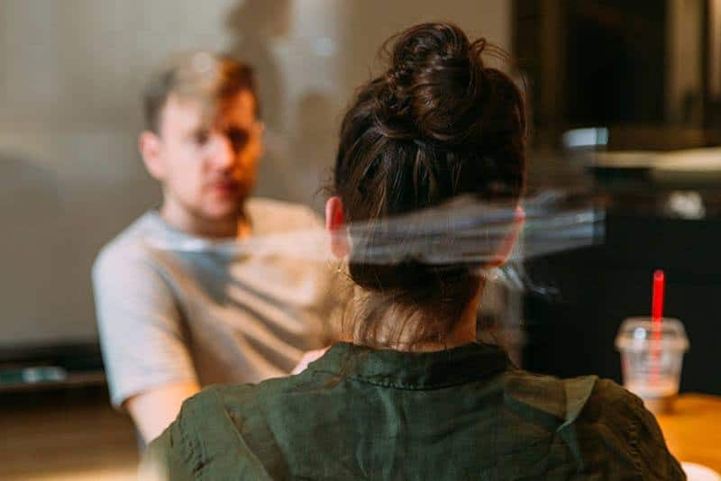 shallow focus photo of man and woman talking in cafe