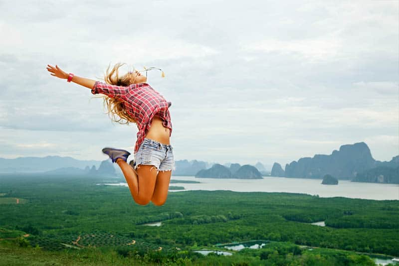 Happy young woman jumping carefree in the mountains