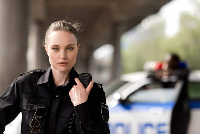 Policewoman using walkie-talkie and looking at camera