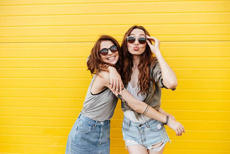 Two young happy women friends looking at camera blowing kisses