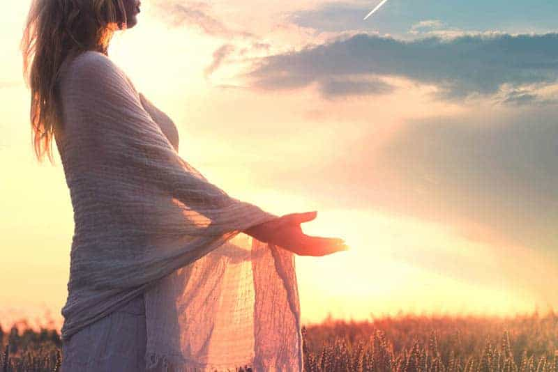 side view of woman standing in field during sunset