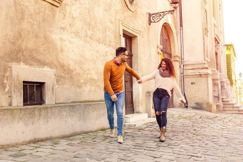 smiling couple holding hands on the street