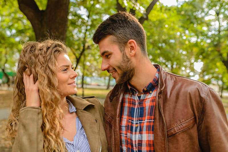 smiling man and woman looks at each other eyes