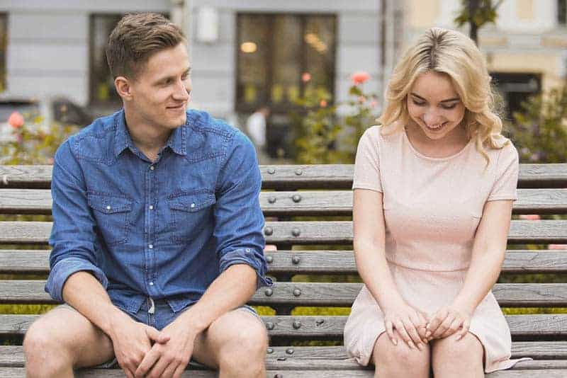 smiling shy couple sitting on the park bench