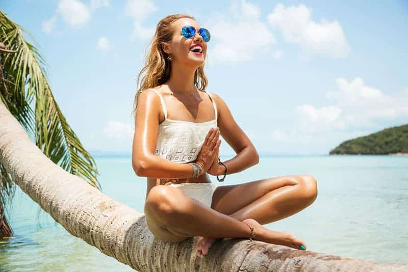 smiling woman meditating while sitting on the beach tree