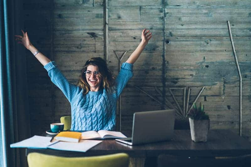 smiling woman raising hands in office