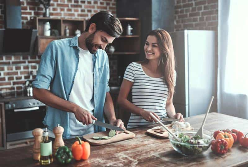 smiling young couple cooking together at home