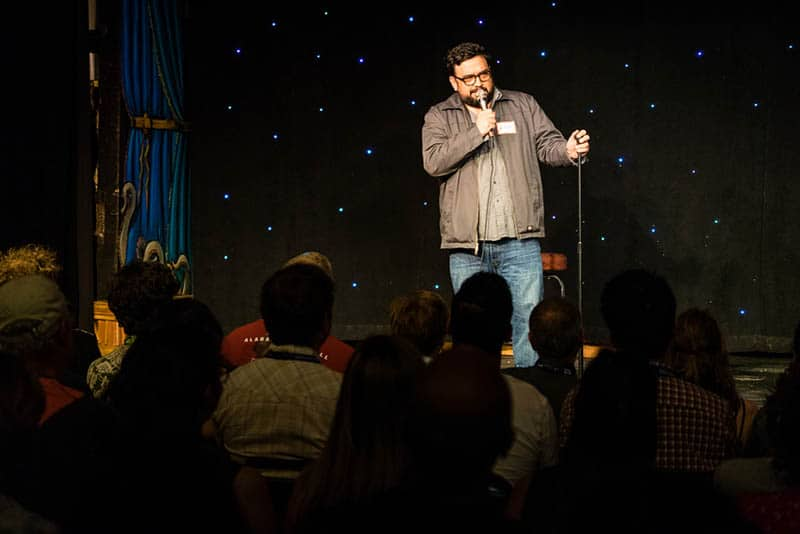 stand up comedian performing in front of crowd