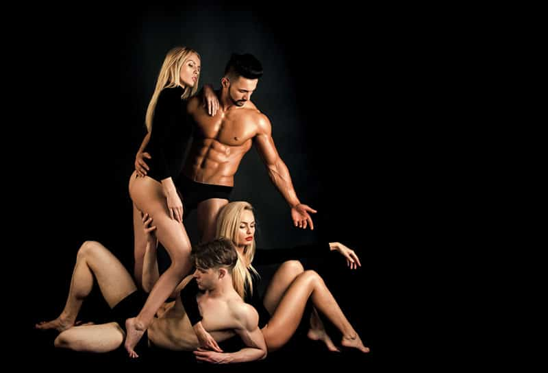 two male and two female in underwear with black background