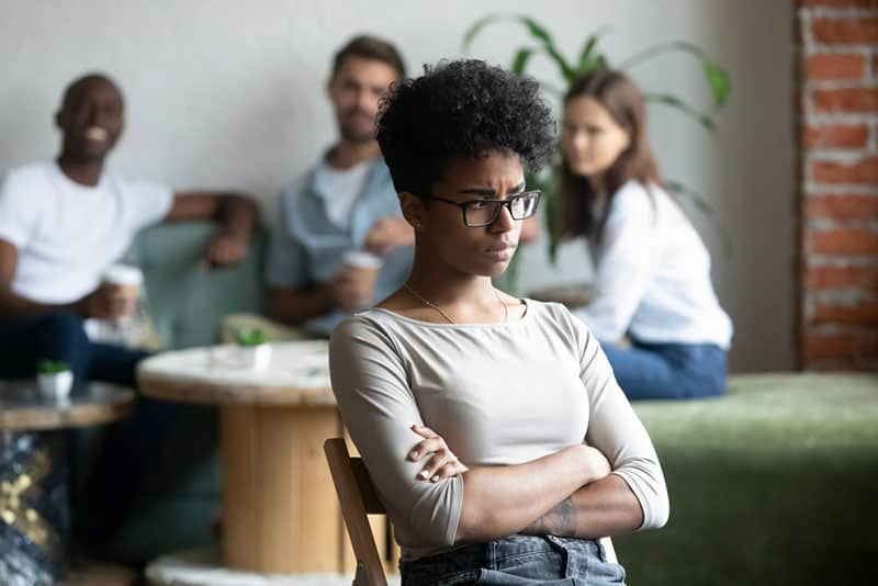 upset woman sitting in front of smiling friends