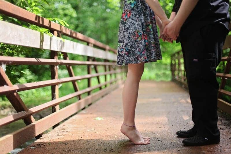 woman barefoot holding hands with her boyfriend