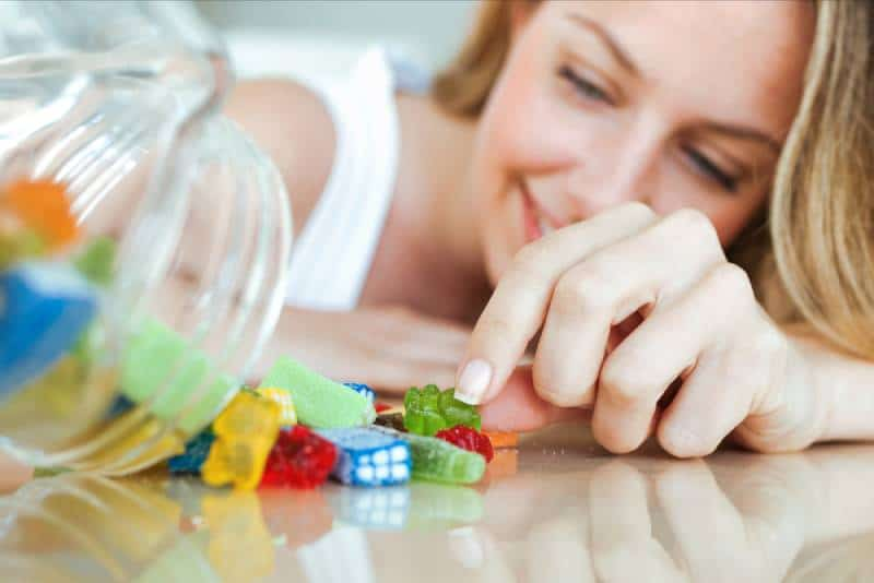 woman eating colorful jelly candies at home