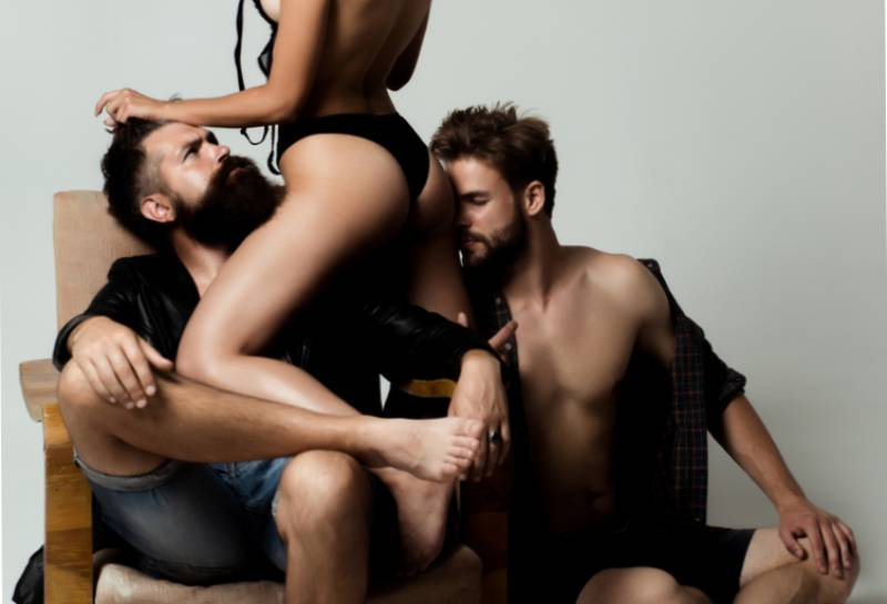 woman in underwear with two men