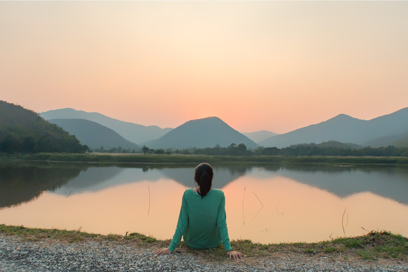 woman is sitting alone by the lake