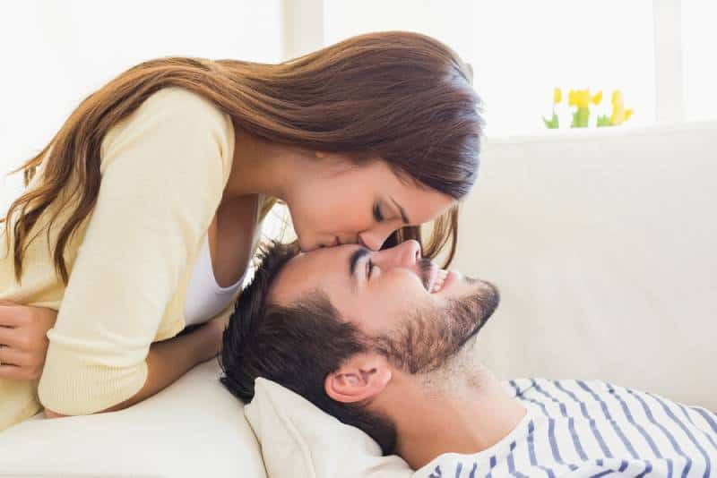 woman kissing man on forehead at home in living room