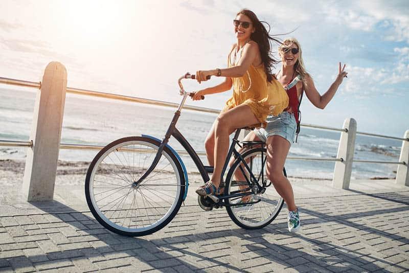woman riding bike while her female friend is on back of bike