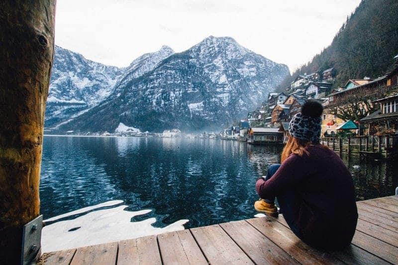 woman sitting alone on wooden dock