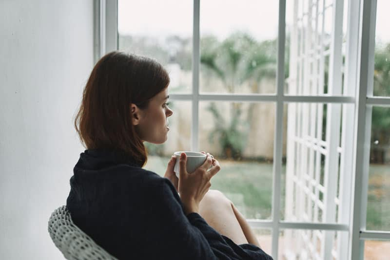 worried woman drinking coffee by the window