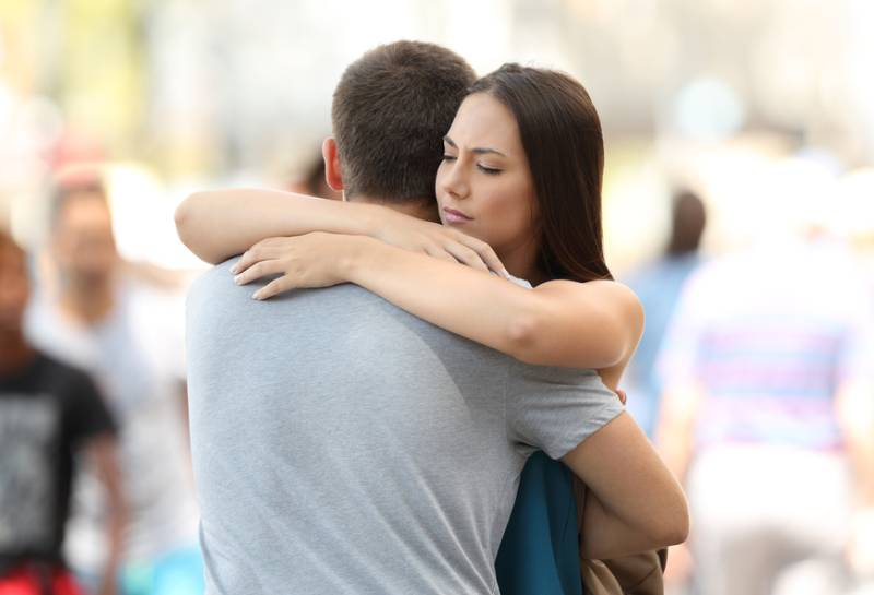 worried woman hugging her boyfriend outside