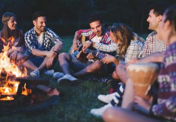 happy friends sitting beside bonfire