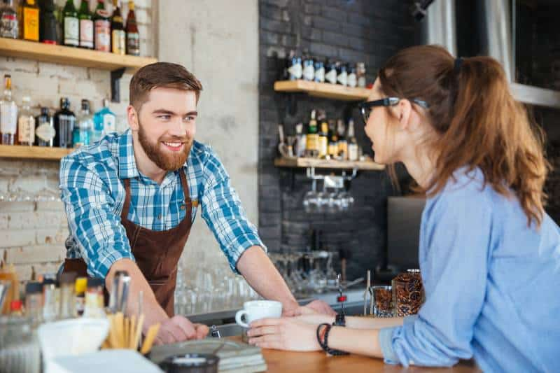 Smiling barista and young pretty woman in glasses chatting in a cafe