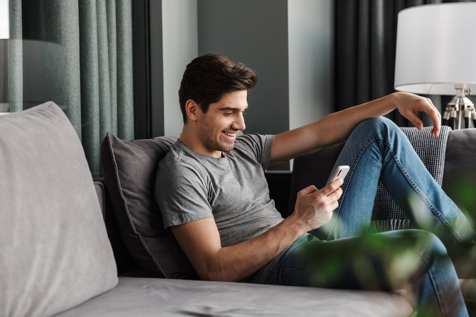 an attractive smiling man sits on a sofa and uses a smartphone