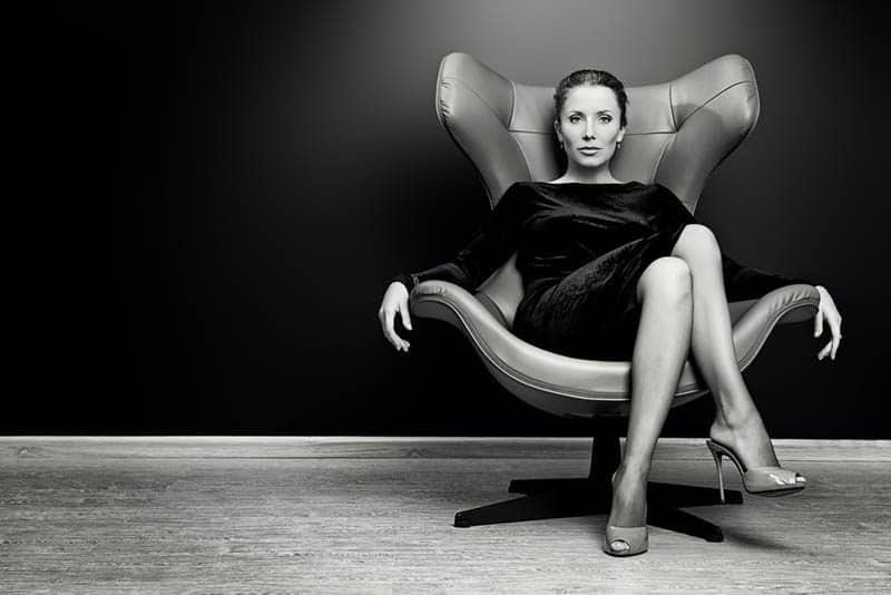 black and white photo of woman sitting on chair with crossed legs