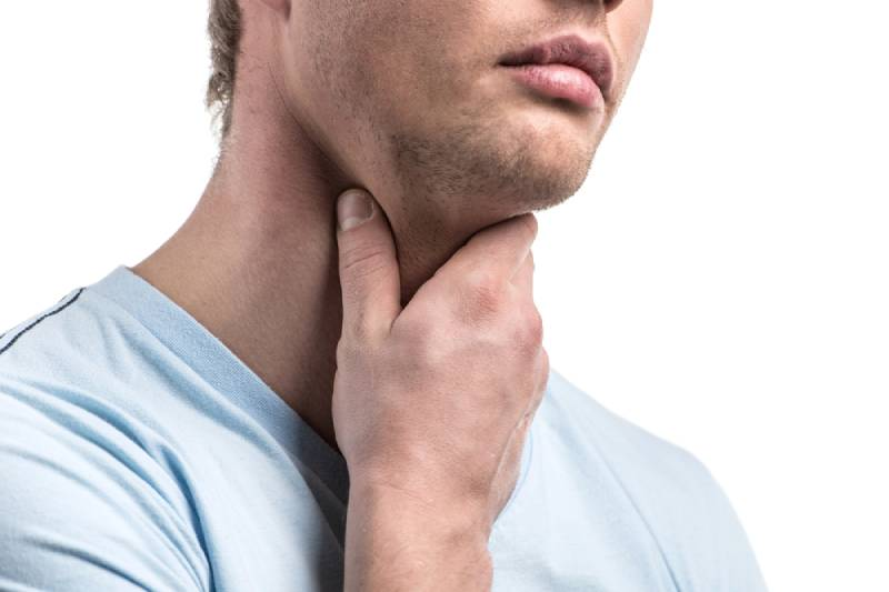 close up man touches his throat