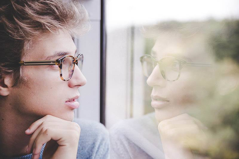 close up portrait of man with glasses looking out
