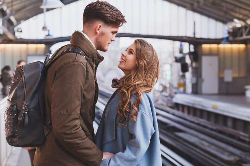 couple holding their hand and looking each other at train station