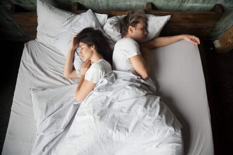 couple sleeping on bed with their backs to each other in bedroom