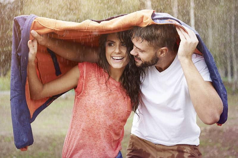 couple under jacket during rain