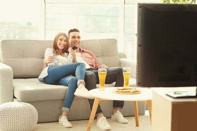 couple watching TV and drinking beer