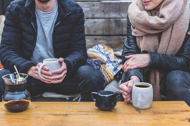 couple wearing jacket and holding cup of tea in cafe
