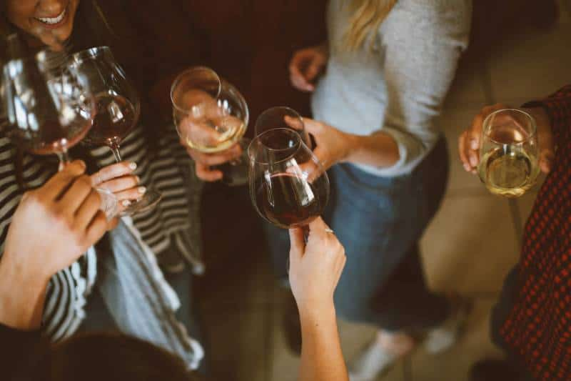 group of friends cheering with glasses of wine