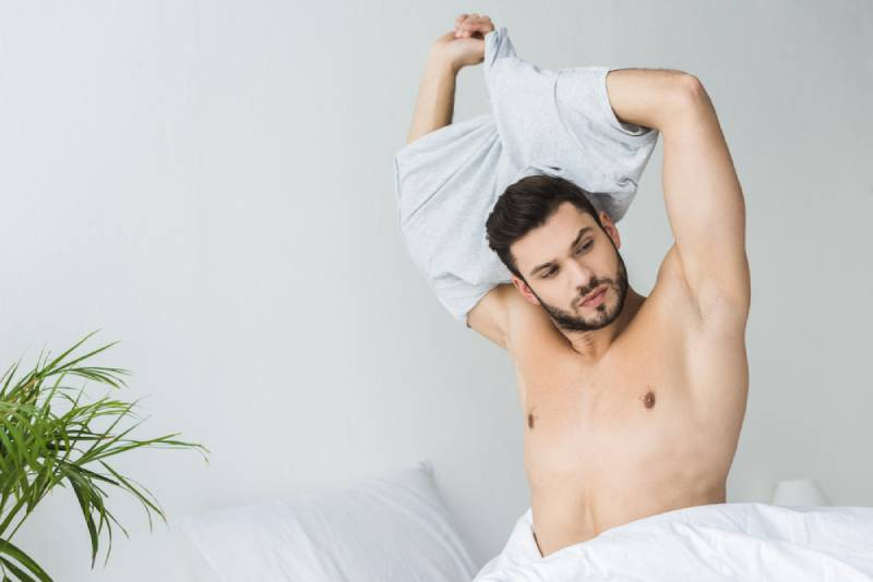 handsome man taking off shirt at home