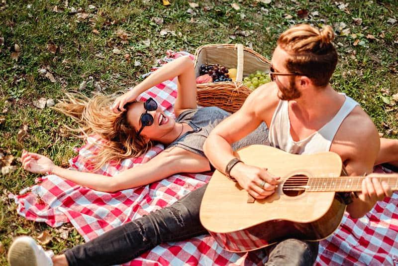 man playing guitar to smiling woman during picnic time