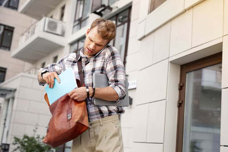 man putting book in bag in front of building