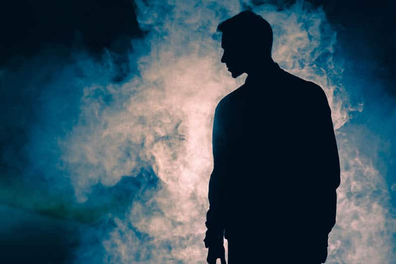 silhouette of man in front of smoke